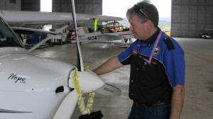 Photo Caption - Michael Combs shares an emotional moment with his REMOS aircraft named Hope One as he quietly reflects on the completion of his epic 40,000 mile, 50 state journey.