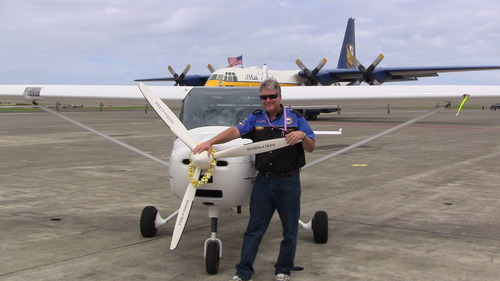 "Photo Caption - Michael Combs and his REMOS aircraft named ""Hope One"" with the Blue Angels ""Fat Albert"" in the background after successfully completing the Fifty State adventure in Kaneohe Bay, Hawaii."